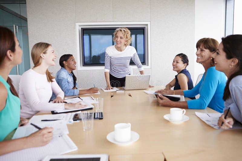 Gruppe Geschäftsfrauen, die um Sitzungssaal-Tabelle sich treffen stockfoto