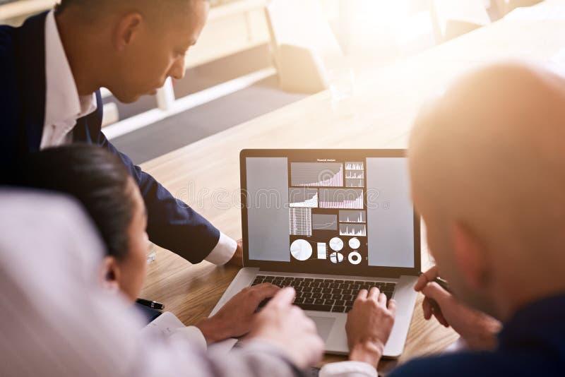Gruppe Geschäftsleute, die Diagramme auf einem Laptop betrachten lizenzfreie stockfotografie