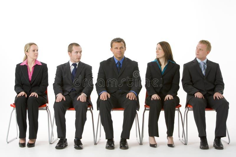 Gruppe Geschäftsleute, die in einer Zeile sitzen lizenzfreie stockbilder