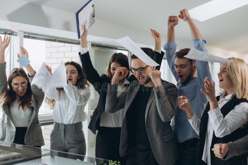 Gruppe Gesch?ftsleute, die feiern, indem sie ihre Gesch?ftspapiere werfen und Dokumente fliegen in einer Luft, Energie von Zusamm stockfoto