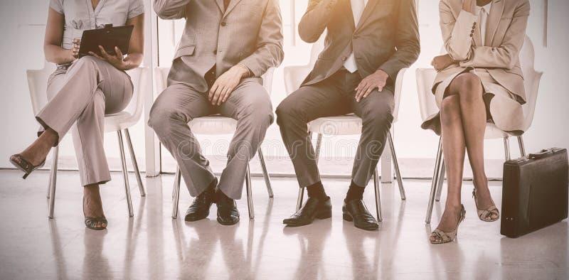 Gruppe Geschäftsleute, die im Warteraum sitzen lizenzfreie stockfotografie