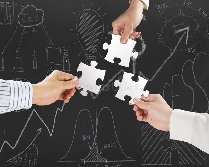 Gruppe Geschäftsleute, die leere weiße Puzzlen zusammenbauen stockfoto