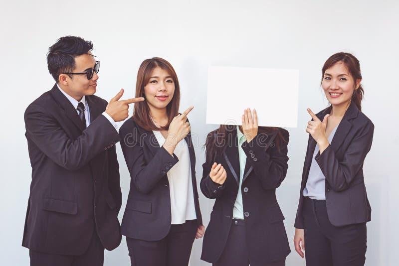 Gruppe Geschäftsleute, die mit weißem Brett aufwerfen stockfotografie