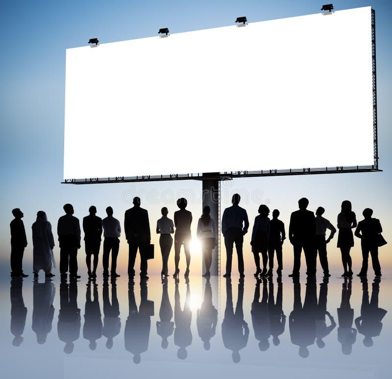 Gruppe Geschäftsleute, die Plakat lesen lizenzfreie stockfotos