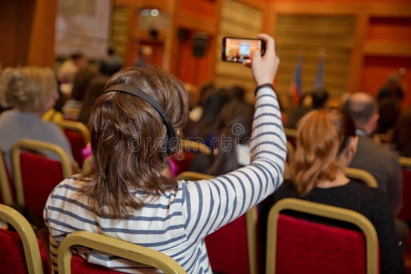 Gruppe Geschäftsleute, die an Pressekonferenz oder Darstellung teilnehmen Unerkennbare Leute, die in den Ohrkopfhörern für verwen stockbilder