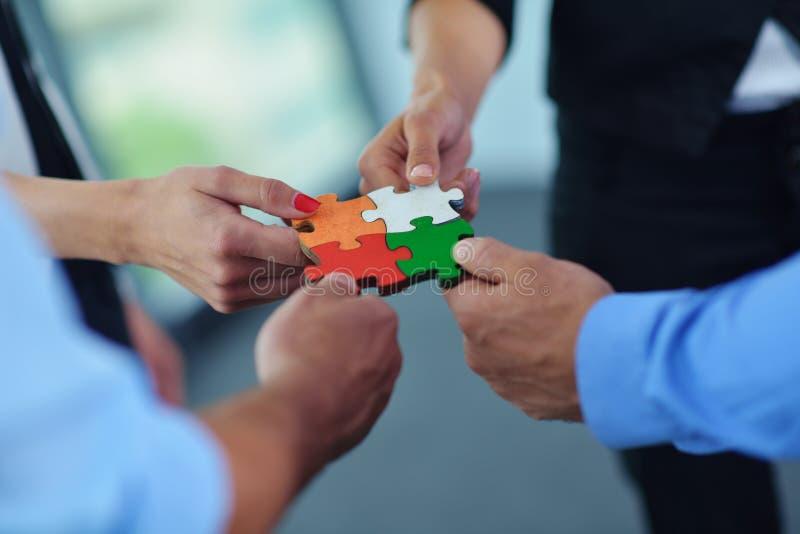 Gruppe Geschäftsleute, die Puzzlen zusammenbauen lizenzfreie stockfotos