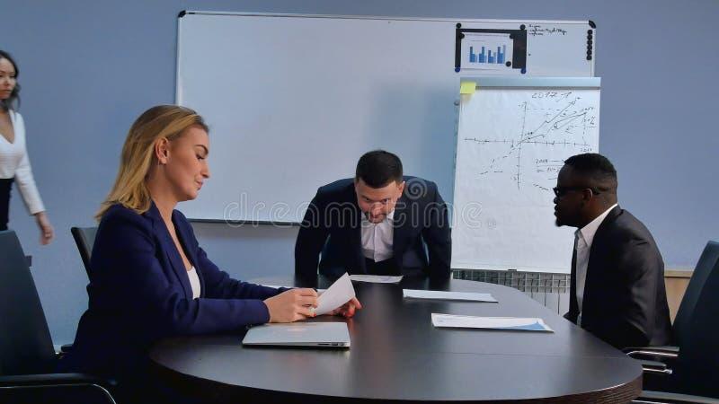 Gruppe Geschäftsleute, die zu einem Büro, placec nahe dem Schreibtisch nehmend kommen und bereiten sich für eine Sitzung vor lizenzfreies stockfoto