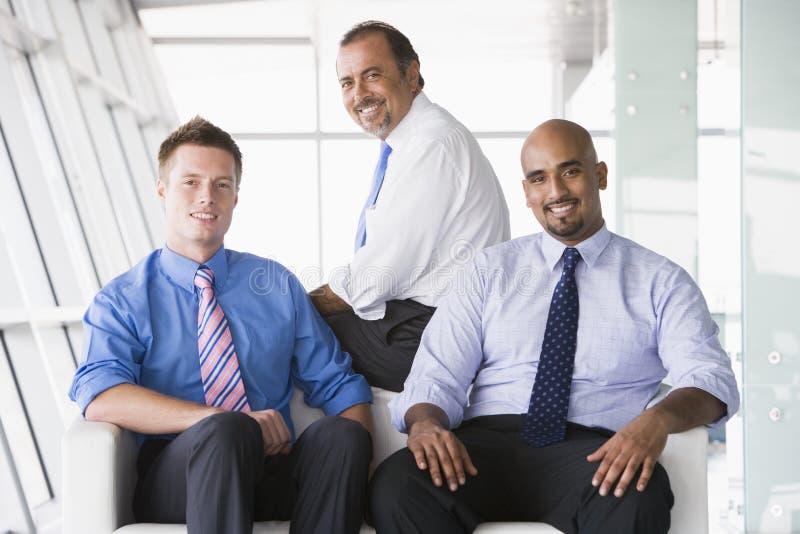 Gruppe Geschäftsmänner, die in der Vorhalle sitzen stockfoto