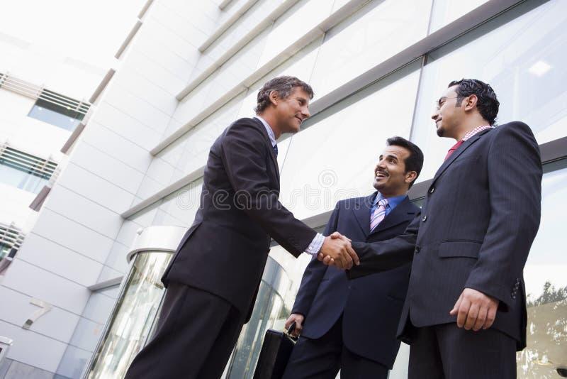 Gruppe Geschäftsmänner, die Hände außerhalb des Büros rütteln lizenzfreies stockfoto
