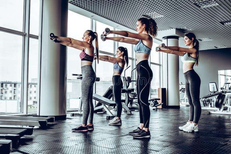 Gruppe glückliche Frauen mit den Dummköpfen, die Muskeln in der Turnhalle biegen stockbild