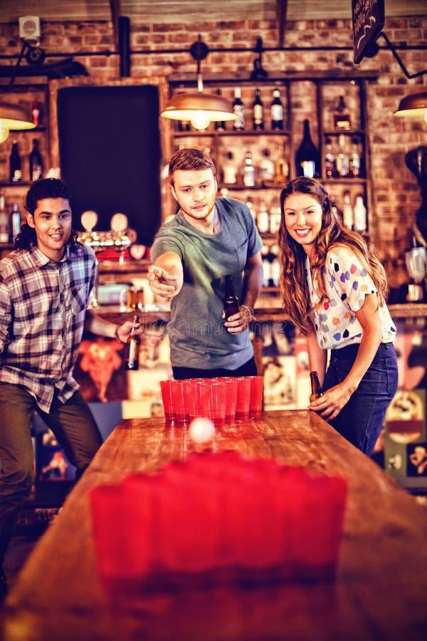 Gruppe glückliche Freunde, die Bier pong Spiel spielen stockfotos