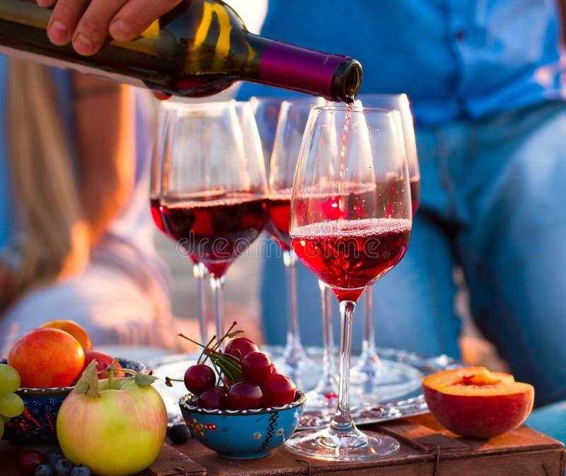 Gruppe glückliche Freunde, die Rotwein auf dem Sonnenuntergangstrand essen stockfoto