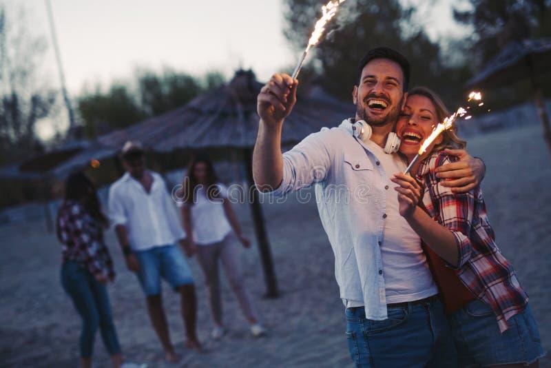 Gruppe glückliche Freunde, die Spaß auf Strand nachts haben stockfoto