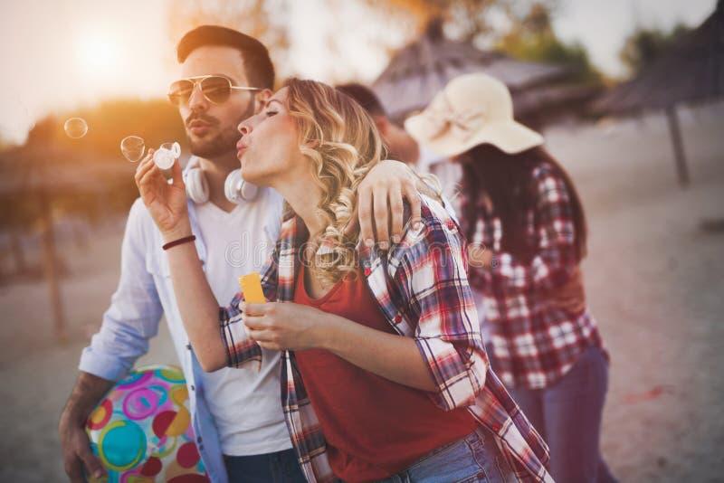 Gruppe glückliche Freunde, die Spaß am Strand im Sommer haben lizenzfreie stockfotografie