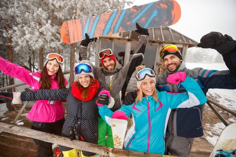 Gruppe glückliche Freunde am kalten Wintertag am Gebirgshäuschen lizenzfreies stockfoto