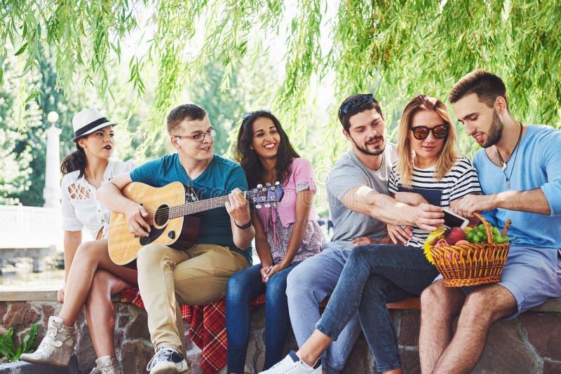 Gruppe glückliche Freunde mit Gitarre Während eins von ihnen Gitarre spielt und andere geben ihm einen Beifall lizenzfreie stockbilder
