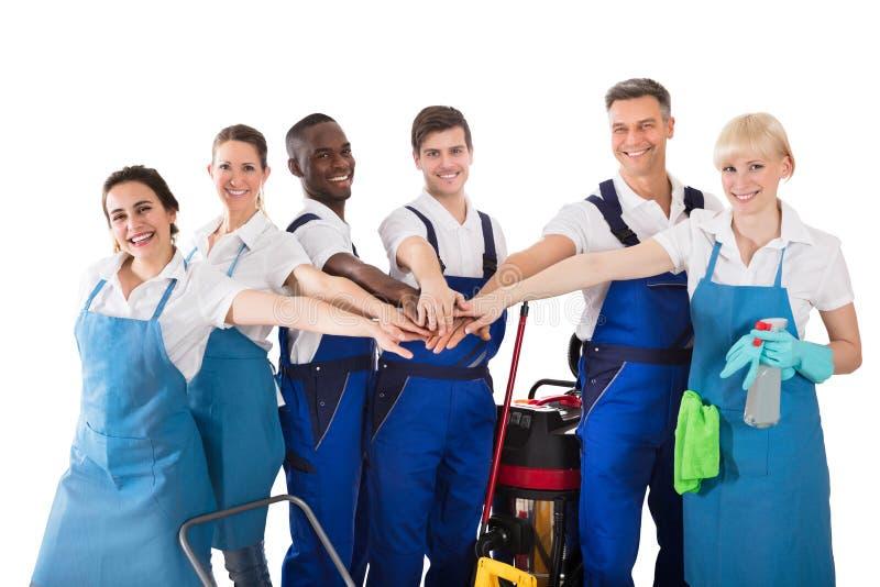 Gruppe glückliche Hausmeister, die Hände stapeln lizenzfreies stockfoto