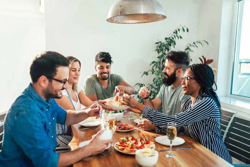Gruppe glückliche junge Freunde, die zu Hause Abendessen genießen stockfotos