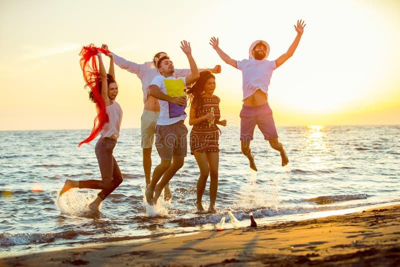 Gruppe glückliche junge Leute, die am Strand auf schönem Sommersonnenuntergang tanzen stockfotografie