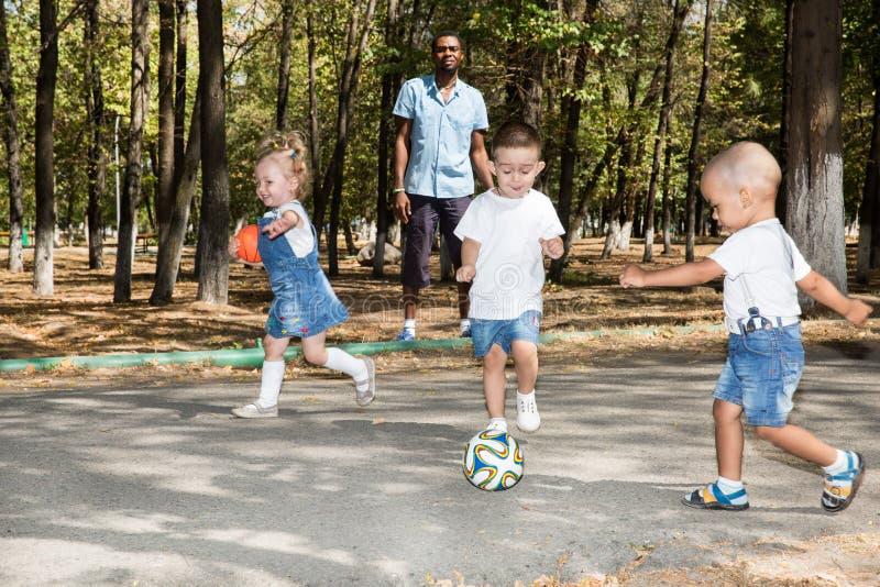 Gruppe glückliche Kinder, die mit Fußball im Park auf Natur am Sommer spielen stockfotografie