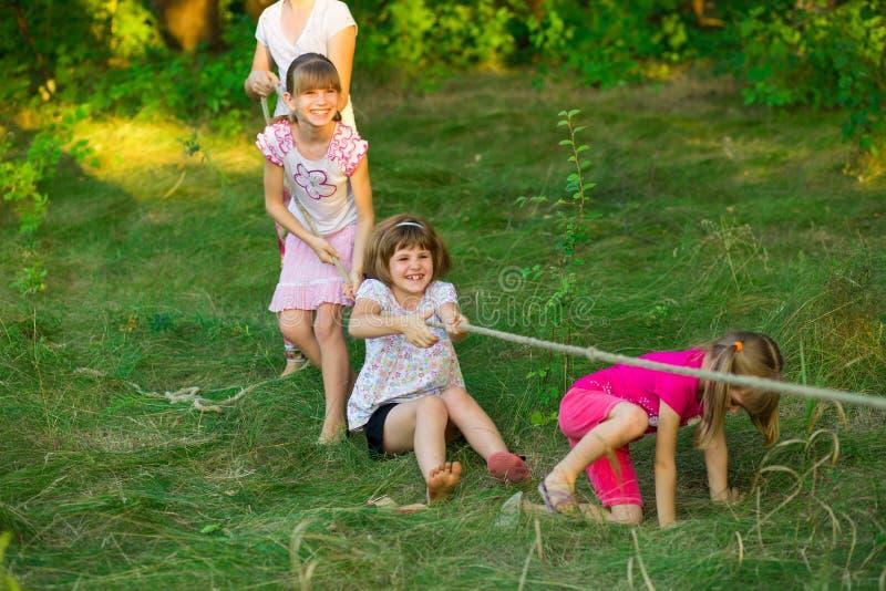 Gruppe glückliche Kinder, die Tauziehen draußen auf Gras spielen stockbild