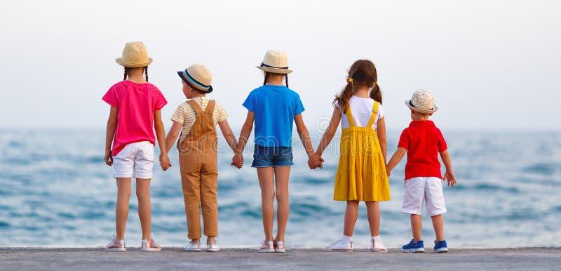 Gruppe glückliche Kinder durch Meer im Sommer lizenzfreie stockbilder