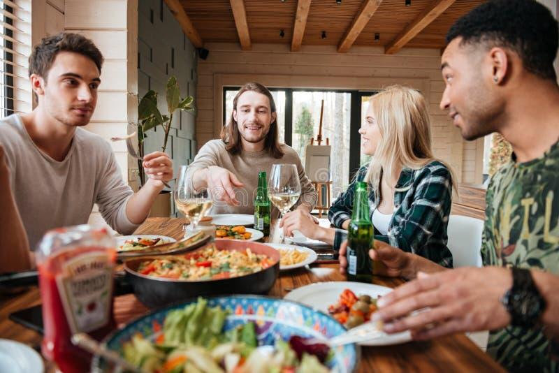 Gruppe glückliche lächelnde gemischtrassige essende, trinkende und sprechende Freunde stockbild