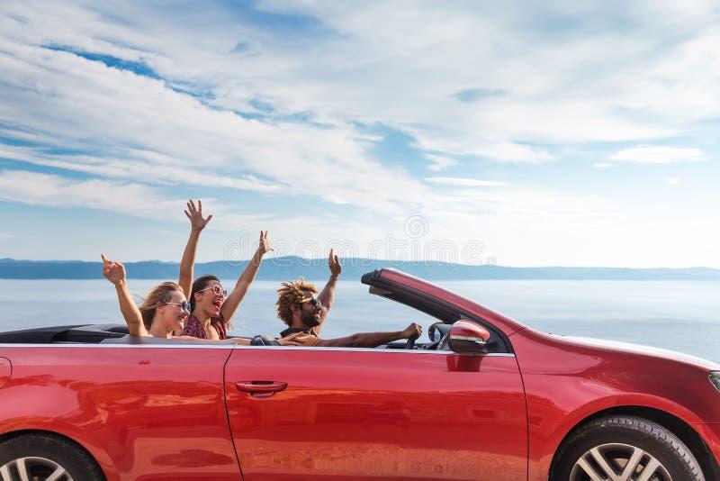 Gruppe glückliche Menschen im roten konvertierbaren Auto stockfotografie
