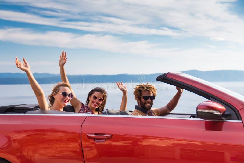 Gruppe glückliche Menschen im roten konvertierbaren Auto lizenzfreie stockbilder