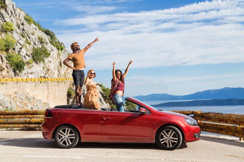 Gruppe glückliche Menschen im roten konvertierbaren Auto stockbilder
