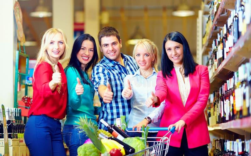 Gruppe glückliche Menschen im Supermarkt, Daumen oben stockfotografie