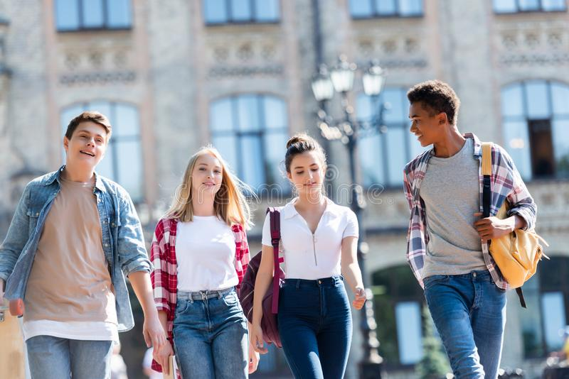 Gruppe glückliche multiethnische Jugendliche mit den Rucksäcken, die haben lizenzfreies stockbild