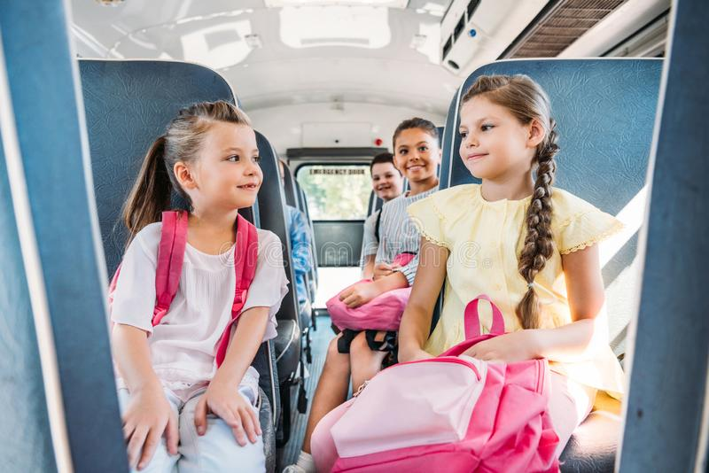 Gruppe glückliche Schüler, die auf Schulbus während fahren lizenzfreie stockfotos