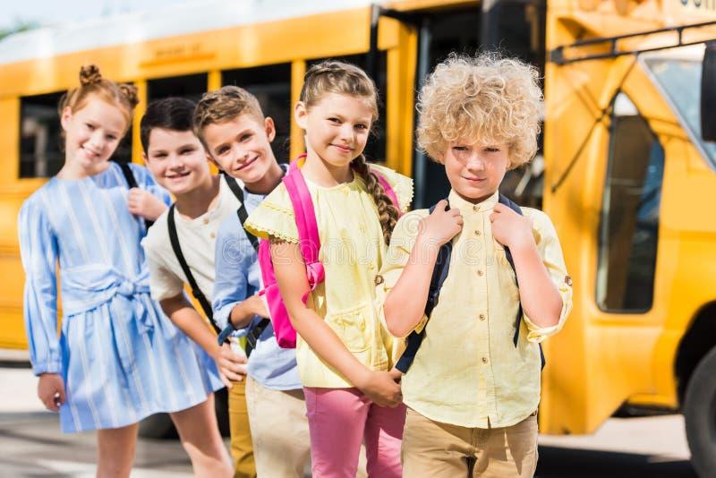 Gruppe glückliche Schüler, die Kamera bei der Stellung in der Reihe vor betrachten lizenzfreie stockfotos