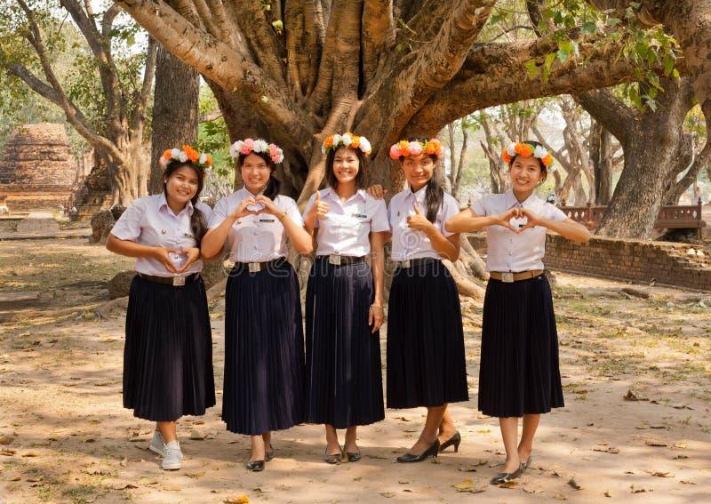 Gruppe glückliche thailändische Mädchen mit Blumenkranz laden Gäste ein, das Land zu besichtigen stockfotografie
