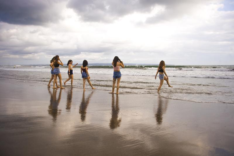 Gruppe glückliche und aufgeregte junge Frauen, die genießen, Spaß auf schönem Sonnenuntergangstrand in FreundinSommerferien haben lizenzfreie stockfotografie