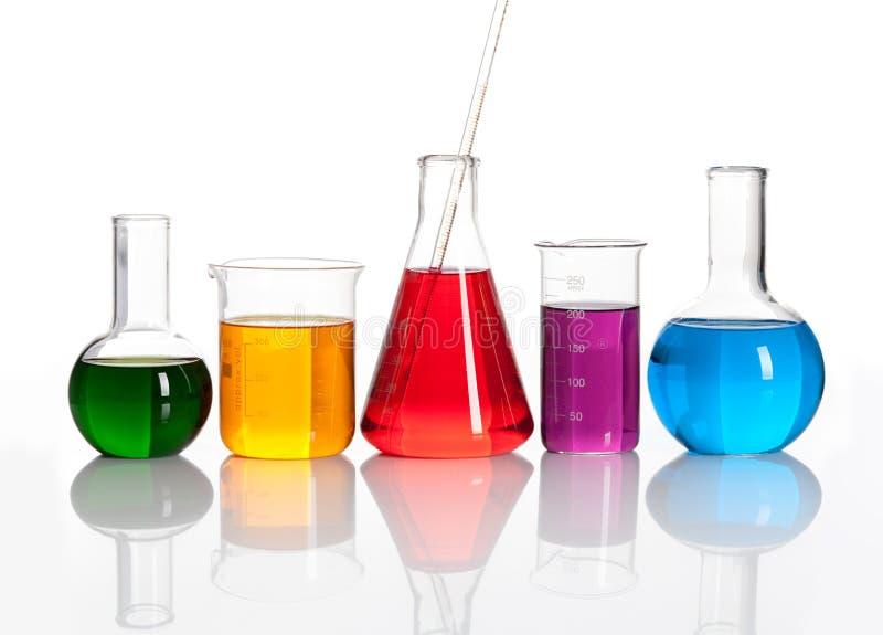 Gruppe Glasflaschen mit farbige liqiuds stockbilder