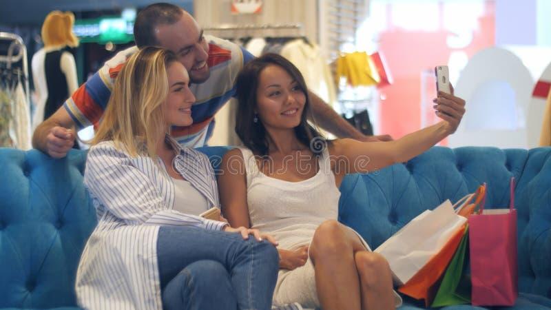 Gruppe Hippies im Einkaufszentrum, das selfie unter Verwendung des intelligenten Telefons nimmt stockbild
