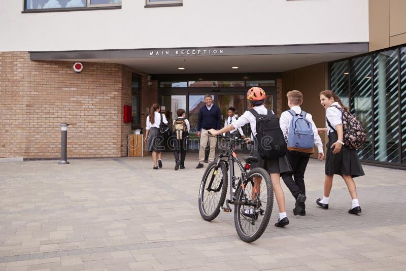 Gruppe hohe Schüler, die einheitliches in der Schule ankommen gehende oder Reitenfahrräder gegrüßt wird vom Lehrer tragen lizenzfreie stockfotografie