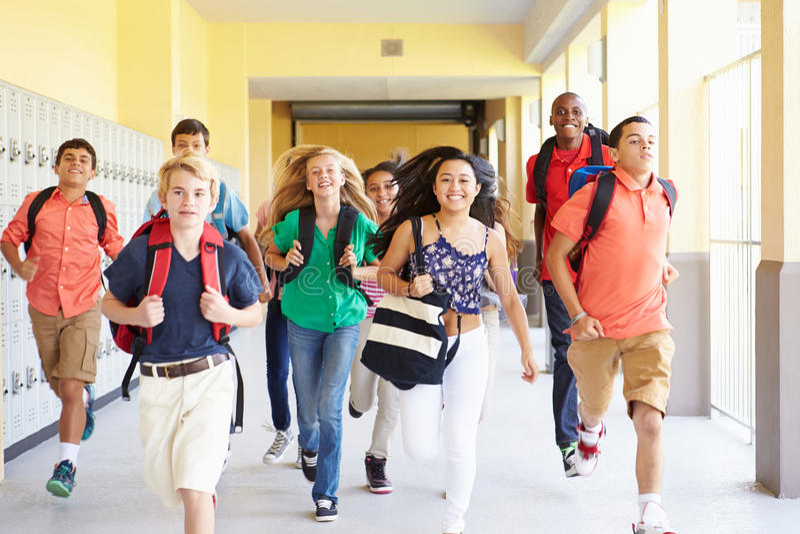 Gruppe hohe Schüler, die entlang Korridor laufen lizenzfreie stockbilder