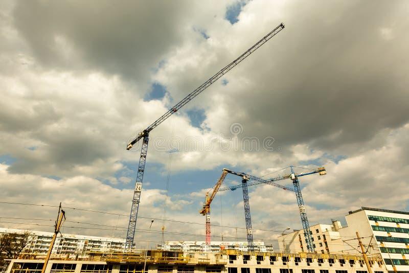 Gruppe hohe Turmkrane arbeiten an dem Bau des Neubaus lizenzfreies stockfoto