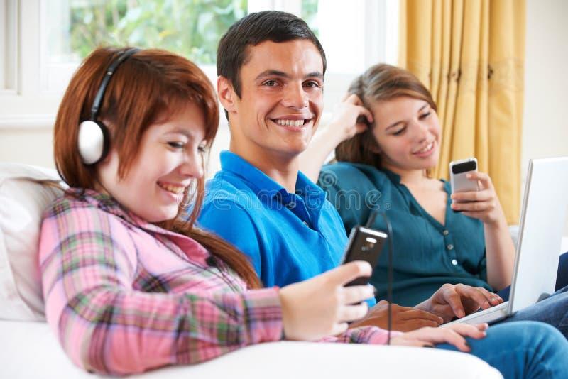 Gruppe Jugendfreunde, die zu Hause Technologie genießen lizenzfreie stockfotos