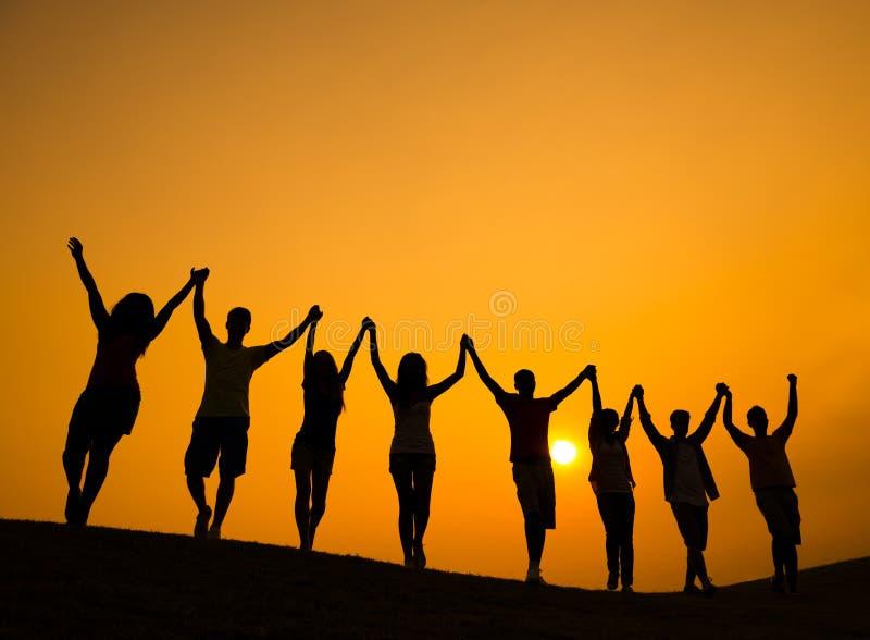 Gruppe Jugendlich-Händchenhalten und feiern in hintergrundbeleuchtetem lizenzfreies stockbild