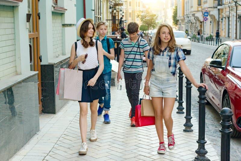 Gruppe Jugendliche mit Einkaufstaschen auf Stadtstraße stockfoto