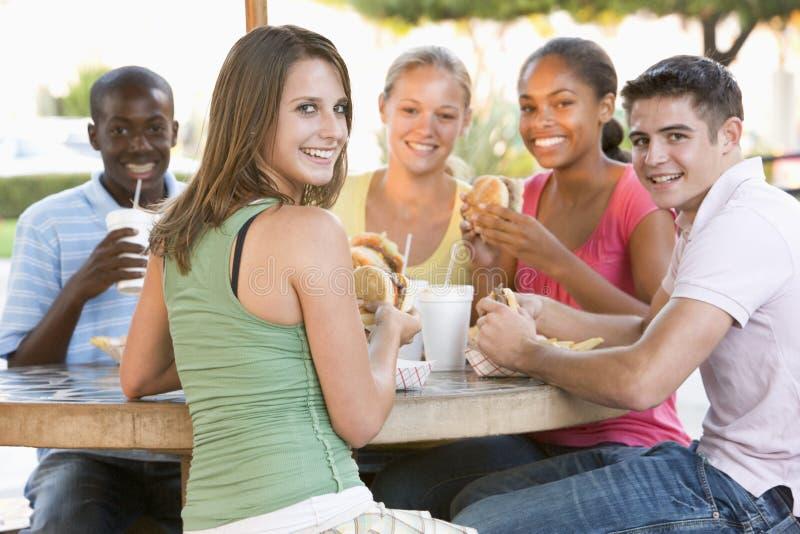 Gruppe Jugendlichen, die draußen sitzen lizenzfreies stockfoto