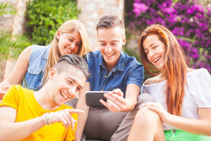 Gruppe Jugendlichen, die ein intelligentes Telefon lachen und betrachten stockbild