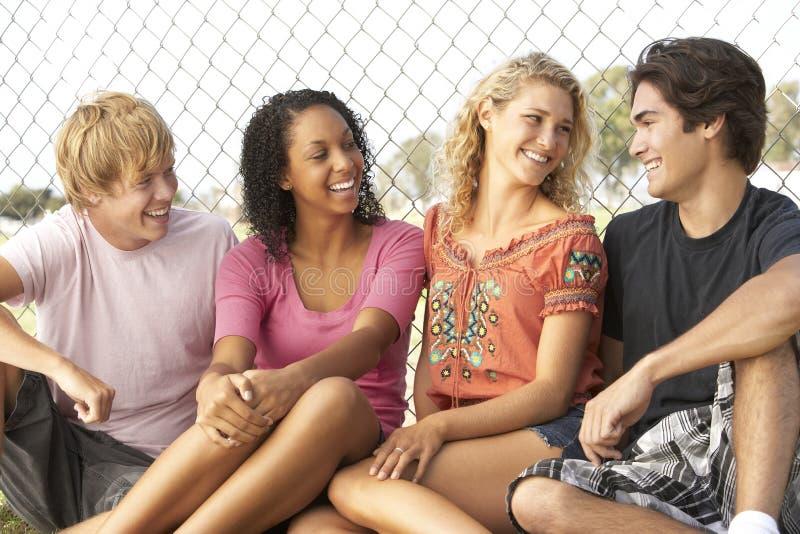 Gruppe Jugendlichen, die im Spielplatz sitzen lizenzfreie stockbilder