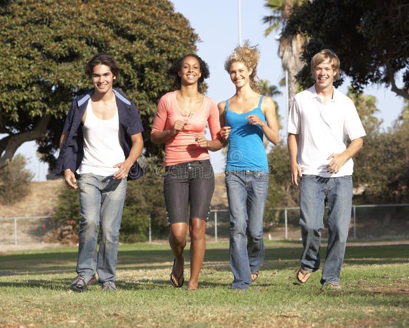 Gruppe Jugendlichen, die in Park laufen lizenzfreies stockbild