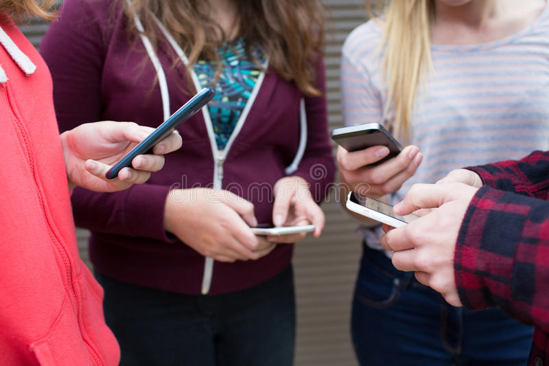 Gruppe Jugendlichen, die Textnachricht an den Handys teilen lizenzfreie stockfotografie