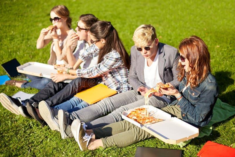 Gruppe Jugendstudenten, die Pizza auf Gras essen stockbild